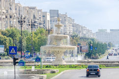 The square Piata Unirii with shops, traffic cars, people. Bucharest, Romania Stock Photos