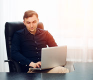 Square picture of leisurely working businessman with laptop on knees Royalty Free Stock Photo