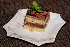Square piece of cake with chocolate and almond on the white plate. Square piece of almond cake with chocolate and almond on the white plate stock photo