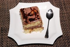 Square piece of cake with chocolate and almond on the white plate. Square piece of almond cake with chocolate and almond on the white plate stock image
