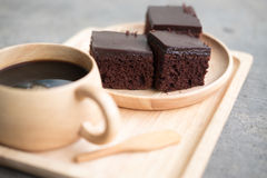 Square piece of chocolate cake with cream filling. On wood plate. Selective focus royalty free stock photo