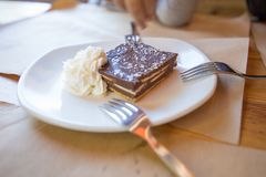 Square piece of chocolate cake with cream. Square piece of brown chocolate cake with cream on white ceramic dish, with three forks for sharing, on paper royalty free stock photos