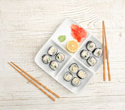 Square plate with rolls on a wooden table, ginger, lemon and wasabi. Top view Royalty Free Stock Photo