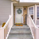 Square Pleasing home with stairs and half hexagon shaped window at the facade. A wreath, doormat, welcome sign, and wall lamp adorn the doorway royalty free stock image