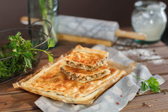 A square potato pie. Potato Square Pie with parsley and greens. A square piece of meat pie on a rectangular meat pie on a wooden surface against the background royalty free stock images
