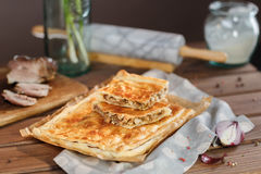 A square potato pie. Potato Square Pie. A square piece of meat pie on a rectangular meat pie on a wooden surface against the background of the ingredients from stock photography