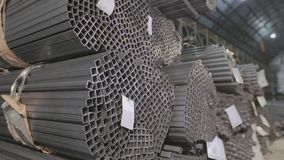 Panoramic view of a large warehouse with metal. Profile pipe in a covered warehouse, profile pipe laid in rows in a. Square profile pipe, metal warehouse. Clean stock video footage
