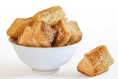 Square Puff Croissant Pastry Zu-Zu Served In Porcelain Bowl Isolated On White Background. Small Square Sesame Puff Pastry Zu-Zu, served in white Porcelain Bowl Royalty Free Stock Images