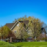 Square Rich green grasses on a vast terrain with houses and trees in the background. A beautiful blue sky can be seen over the scenic landscape on this sunny stock photo
