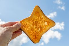 A square ruddy piece of bread for toast in a left woman hand against the blue sky with white clouds on picnic in summer. A square ruddy piece of bread for toast royalty free stock images