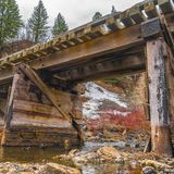 Square Rustic wooden bridge crossing over a rocky stream with clear shallow water royalty free stock image