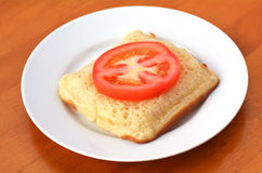 Square shape buttered English crumpet with slice of tomato stock photography