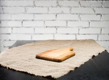 Square in shape wooden cutting board on a textile background, sh royalty free stock photo