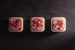 Square shaped strawberry candies on a wooden table. Three different candies on a wooden table viewed from above Royalty Free Stock Images