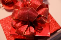 Square shiny red gift box with gritter red ribbon bow, selective focus and blurred background. Closed up a square shiny red gift box with gritter red ribbon bow Stock Images