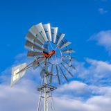 Square Shiny steel windpump against a vibrant blue sky with cottony clouds stock images