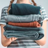 Square shot of a Girl teenager with two braids holding a pile of clothes, isolated on gray background Royalty Free Stock Photography