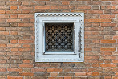 Square small window with white frame on brick wall Stock Photo