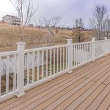 Square Spacious balcony of a home with wooden floor and white railing. The balcony has a view of houses on an expansive grassy slope under the cloudy blue sky royalty free stock photo