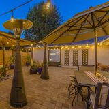 Square Stone brick patio of a home illuminated with string lights and lamp posts. The open air dining area is under an umbrella while the seating area is under royalty free stock image