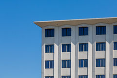 Square Stone Building Under Clear Blue Sky. A white stone condo or apartment building under clear blue skies Royalty Free Stock Images