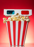 The square striped box with popcorn and 3D glasses on a red Royalty Free Stock Photos