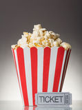 The square striped box with popcorn and movie ticket on a gray Royalty Free Stock Photos