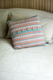 Square Throw Pillow in Crocheted Case on Bed. A square throw pilling in a crocheted case, placed in a bed stock photography