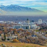 Square Utah State Capital Building and skyscrapers towering over the populous city. Snow capped mountain and cloudy blue sky can be seen in teh scenic stock photos