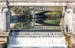 Square waterfall under a bridge. A quiet river flows into a waterfall framed by classic style columns Stock Photos