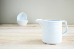 Square white cup over wooden table Royalty Free Stock Images