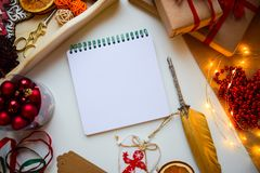 Square white notepad on a white background surrounded by Christmas and New Year trifles, a place to insert text royalty free stock image