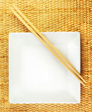 Square White Plate and Chopsticks on a Bamboo Mat Royalty Free Stock Photo