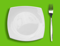 Square white plate and fork on green top view Royalty Free Stock Photography