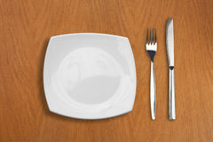 Square white plate, knife and fork on wooden table Stock Image