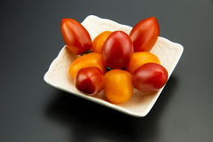 Square white porcelain and small tomatoes Stock Photos
