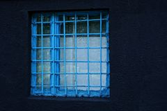 A square window behind a blue lattice on a black concrete wall. Black stone wall with square window behind steel grating Royalty Free Stock Photography