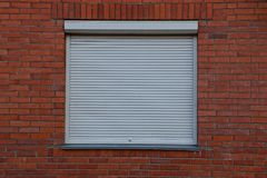 The square window closed by gray jalousie on a brick wall. A large square window closed by gray jalousie on a red brick wall Stock Photos