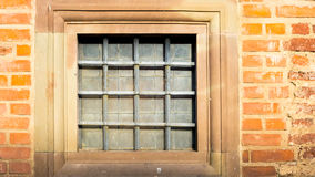Square window with iron grating. And stone jamb in ancient castle Royalty Free Stock Photo