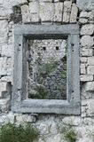 Square window in a stony wall of old ruins in Slovenia. Square window in a stony wall of an abandoned old fort ruins in Slovenia Royalty Free Stock Images