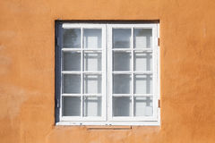 Square window in white wooden frame. Yellow wall background photo texture Royalty Free Stock Photo
