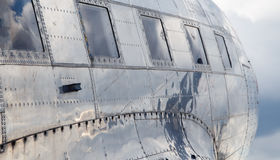 Square windows of the old airplane sunny day reflection of the sky in an aluminum casing Royalty Free Stock Photo