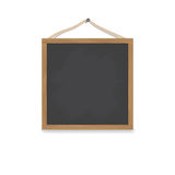 A square wooden chalkboard hangs on a nail on a rope. Board for a menu or drawing. Royalty Free Stock Photos
