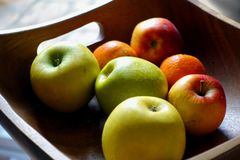 Square wooden fruit bowl containing imperfect red and green apples, and oranges.  royalty free stock images