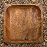 Square wooden plate top view against stones Stock Image