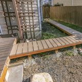 Square Wooden walkway inside the yard of a home viewed on a sunny day. The walkway is connected to a wooden deck with a reflective glass door leading inside stock photography