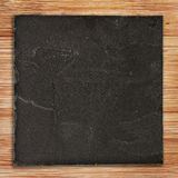 Squared black slate on wood Royalty Free Stock Image