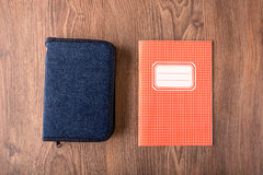 Squared exercise book and pencil case on wooden background Stock Photography