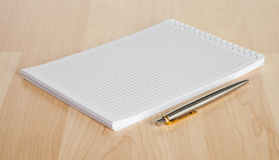 Squared paper loose-leaf note sheet on the table Royalty Free Stock Photography