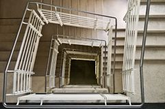 Squared stairs. Symetrical square staircase looking downwards. metal handle rail marble slab flooring typical institutional interior of modern europe stock photo